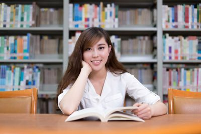 Beautiful asian female student read book in library with bookshelf as background.